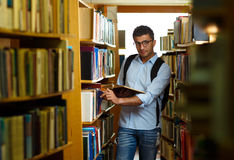 Student reading book between the shelves in the library. Young arab student reading book between the shelves in the library Stock Images