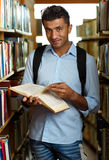 Student reading book between the shelves in the library Stock Images