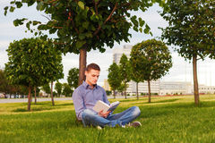 Student reading book sitting in the park under tree on the grass Stock Images