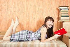 Student reading book on sofa Royalty Free Stock Image