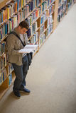 Student reading a book standing in library. At the university Stock Images