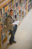 Student reading a book standing in library smiling at camera. At the university Royalty Free Stock Photo