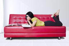 Student reading books while lying on sofa Stock Photography