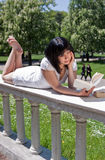 Student reading books in the park. Young female with white dress is reading books in the park stock photos