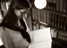 Student reading at bookshelf, B&W Stock Images