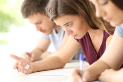 Student reading a cheating sheet during an exam. Bad student reading a cheating sheet during an exam in a classroom Stock Image