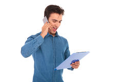 Student reading clipboard notes and talks on the phone. Casual student reading on clipboard and talks on the phone on white background Royalty Free Stock Photo