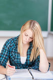 Student Reading Documents At Classroom Desk Royalty Free Stock Photos