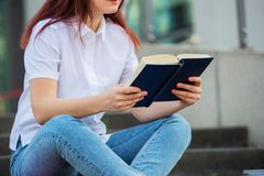 Student reading her favorite book. Female university student outdoors on Campus holding books. Confident student holding books over university building stock image
