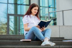 Student reading her favorite book. Female university student reading outdoors on Campus holding books. Confident student holding books over university building royalty free stock image