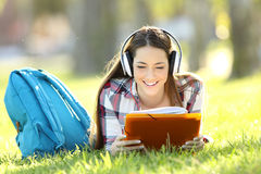 Student reading notes and listening an audio tutorial. Front view portrait of a student reading notes and listening an audio tutorial on line lying on the grass Royalty Free Stock Image