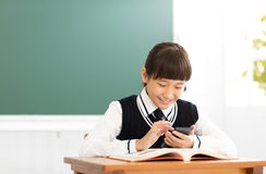 Student reading smart phone in classroom Stock Photo