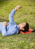 Student Reading Text Message On Mobilephone At. Side view of young male student reading text message on mobilephone while lying on grass at college campus Royalty Free Stock Photos