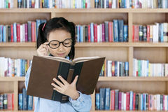 Student reading textbook in library Stock Photo