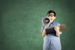 Student reading textbook with a megaphone. Image of boy student wearing glasses while reading textbook with a megaphone in the class Royalty Free Stock Image