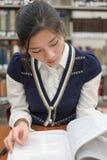 Student reading textbook near bookshelf. Portrait of young female student reading a textbook in front of library bookshelf Royalty Free Stock Images