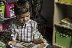 Student Reading. A young male student sitting on the floor reading in a classroom Royalty Free Stock Photo