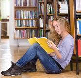 The student reads the book on a floor in library Stock Images