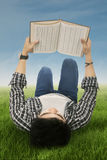 Student reads book outdoors Stock Images