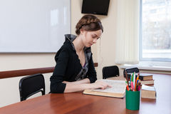 Student reads textbook. Beautiful female student sitting at a desk and reading a textbook Stock Photos