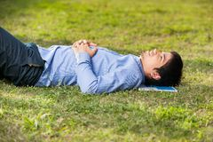 Student Relaxing On Grass At University Campus. Side view of male student relaxing on grass at university campus Stock Photography