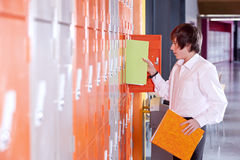Student removing binder from school locker Stock Images