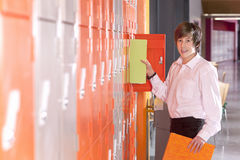 Student removing binder from school locker Stock Image