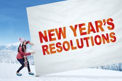 Student with a resolutions banner. Young girl pulling a big banner with a text of new year's resolutions, shot in winter time Royalty Free Stock Image