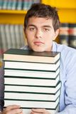 Student Resting Chin On Stacked Books In Library Royalty Free Stock Images