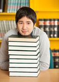 Student Resting Chin On Stacked Books At Table In Stock Photo