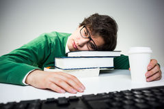 Student resting head on books. Young student in green pullover resting head on book stack placed on white desktop with coffee cup and computer keyboard Royalty Free Stock Photography