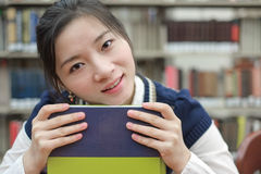 Student resting her chin on textbook Stock Photo