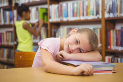 Student resting her head on some books. At the elementary school library Stock Photography