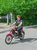 Student rides a moped Royalty Free Stock Image