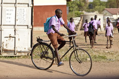 Student riding bicycle in Africa Royalty Free Stock Images
