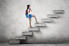 Student with rucksack climbing a stairs. Female college student walking upward on the stairs while carrying a backpack and folder Royalty Free Stock Photo