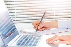 Student ` s übergibt die Herstellung von Anmerkungen nahe bei dem Laptop Lizenzfreie Stockfotografie