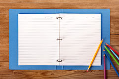 Student desk blank ring binder writing book lined paper copy space. Students desk with blue project folder and various pencils. Space for copy royalty free stock photography