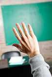 Student's Hand Against Greenboard In Classroom Royalty Free Stock Photos