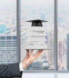 Student's hand is holding a gadget with books and graduation hat on it. Royalty Free Stock Photo