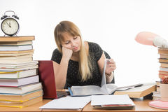 Student sadly looking at turning pages in a folder at the desk among the stacks of books Stock Images