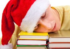 Student in Santa Hat sleep. Young Man in Santa Hat sleep on the Books on a Table Stock Images