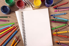 Student school desk with blank open art book, pencils, crayons, copy space Stock Photos