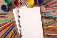Student school desk with blank open art book, pencils, crayons, copy space stock photos