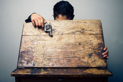 Student at school desk with gun. Student is opening an old school desk to look for something. He has a gun in his hand Royalty Free Stock Photos