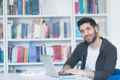 Student in school library using laptop for research Royalty Free Stock Photo
