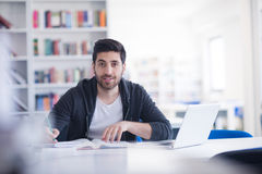 Student in school library using laptop for research Royalty Free Stock Images