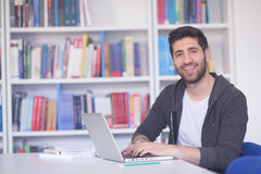 Student in school library using laptop for research Royalty Free Stock Photos