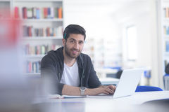 Student in school library using laptop for research Stock Photography