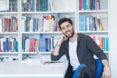 Student in school library using laptop for research Stock Image
